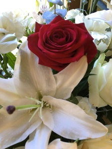 A red rose in the center of a white bouquet is a metaphor for our loved one surrounded by her family.