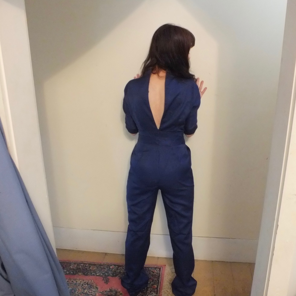 navy blue jumpsuit from an online Shanghai-based company called Rotital a woman with her back to the camera with a gaping zipper on the jumpsuit.
